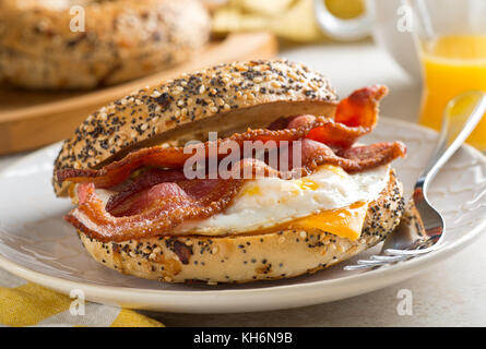 A delicios breakfast bagel with bacon, egg and cheese. - Stock Photo