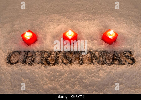 The word Christmas in wooden letters on a snow background illuminated by three red candles. - Stock Photo