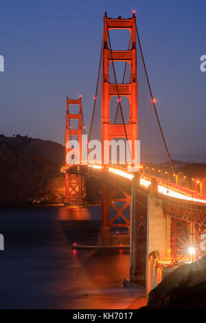 Golden Gate Bridge on a clear evening, as seen from the Presidio. - Stock Photo