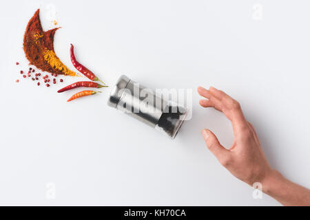 woman reaching for pepper grinder - Stock Photo
