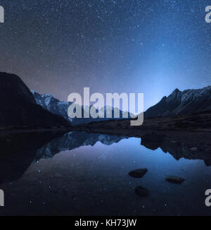 Starry night in Nepal. Amazing night scene with mountains and lake. Landscape with high rocks with snowy peak and - Stock Photo