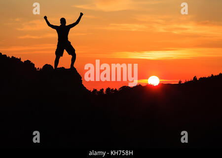Man hiking silhouette in mountains, sunset and clouds. Male climber hiker arms outstretched on top of mountain after - Stock Photo