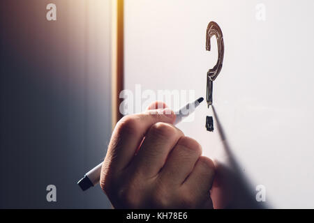 Confused businessman writing question mark on office whiteboard, selective focus - Stock Photo