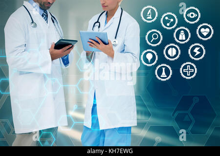 Doctors discussing something on clipboard against curved white room - Stock Photo