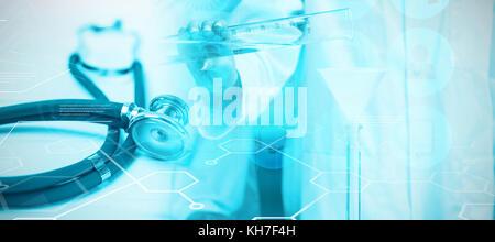 Medical icons set against stethoscope on desk - Stock Photo