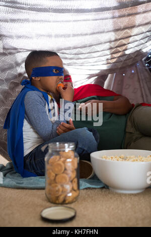Father and son in superhero costume having popcorn at home - Stock Photo
