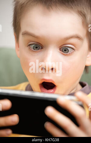 Young boy playing handheld game console - Stock Photo