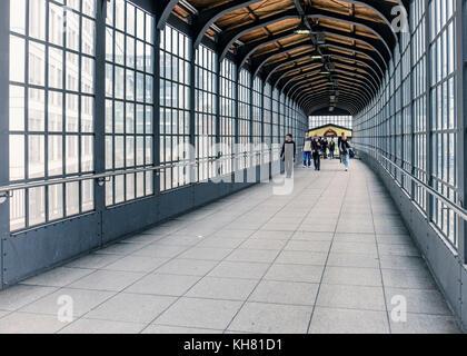 Germany, Berlin,Friedrichstrasse railway station building interior,people walking in historic glass & steel exit - Stock Photo
