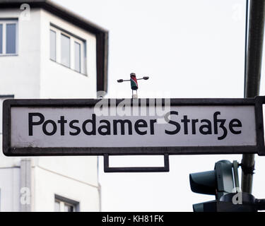 Berlin-Mitte,Tiergarten. Kork Yogi, cork yogi miniature man doing yoga on Potsdamer strasse street sign - Stock Photo