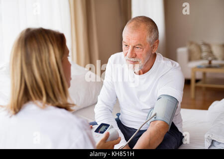 Health visitor and a senior man during home visit. - Stock Photo