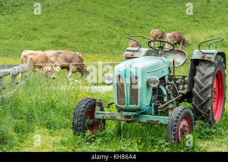 Old tractor on meadow. Beautiful mountain view in the Alps - Stock Photo