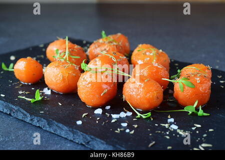 Honey glazed baby carrots with sea salt and thyme on a grey abstract background. Healthy eating concept. Fasting - Stock Photo