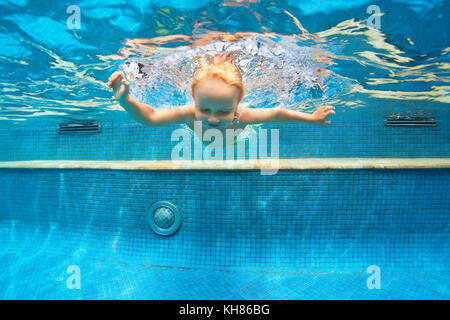 Funny child learn swimming, diving in blue pool with fun - jumping deep down underwater with splashes. Family lifestyle, - Stock Photo