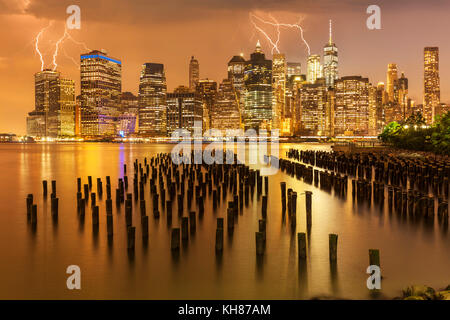 manhattan skyline New York skyline Lightning storm above the skyscrapers with Brooklyn old pier 1 wooden pilings - Stock Photo