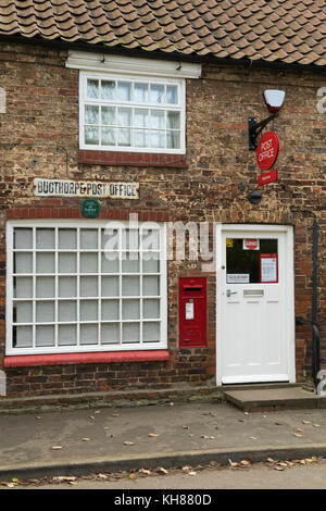 Exterior view of small rural village post office shop (closed today) with post box, signs, windows & doorway - Bugthorpe, - Stock Photo