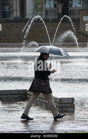 Man walking in the heavy rain, holding umbrella & using phone, passing the Mirror Pool & fountains - Bradford City - Stock Photo