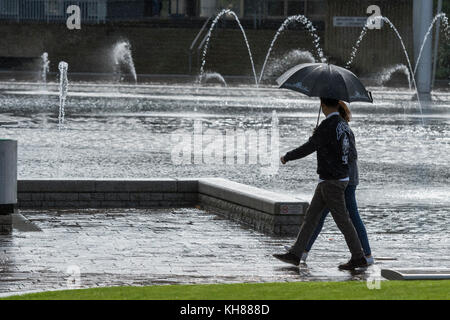 Couple walking in heavy rain, sheltering under umbrella, passing the Mirror Pool & fountains - Bradford centre City - Stock Photo