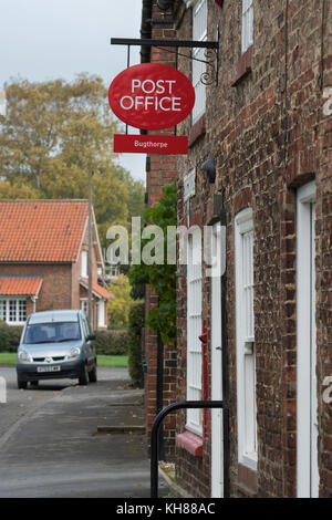 Exterior view of small rural village post office shop (closed today) with post box, red sign, windows & doorway - Stock Photo