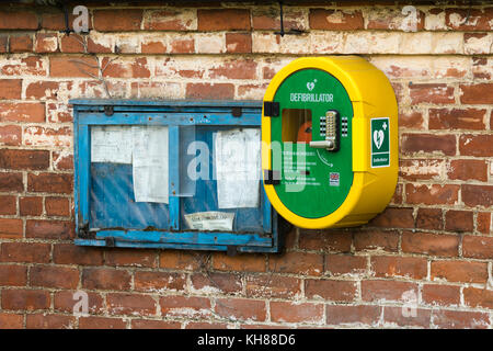 Emergency life saving defibrillator & old village notice board side by side, mounted on external brick wall - Burnby - Stock Photo