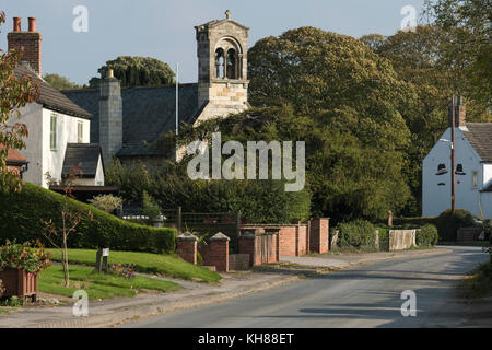 View along quiet, rural country lane towards tall bell tower of St Giles Church & attractive village cottages - - Stock Photo