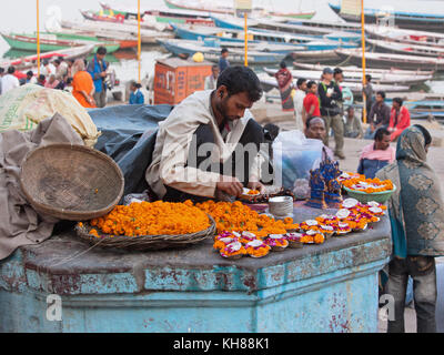 Trader on the banks of the river Ganges selling flower petals, garlands and miniature oil lamps ( deeyas ) for Hindu - Stock Photo