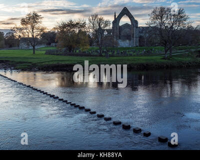 Stepping Stones across the River Wharfe and the Priory Ruins at Dusk Bolton Abbey North Yorkshire England - Stock Photo