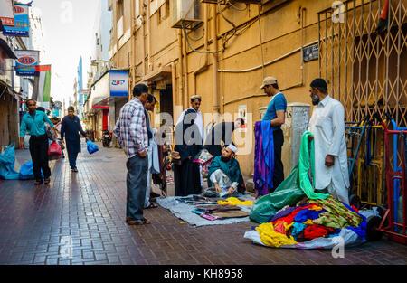 Deira, Dubai, UAE, January 15, 2016: merchants are selling clothes on the street in Deira neighborhood in Dubai - Stock Photo