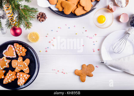 Christmas homemade gingerbread cookies on the white wooden table, christmas background concept. The process of decorating with meringue cream. Selective focus. Space for text, top view