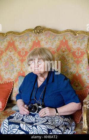 Photographer Jane Bown (13 March 1925 – 21 December 2014), B&W portrait sitting on sofa holding camera - Stock Photo