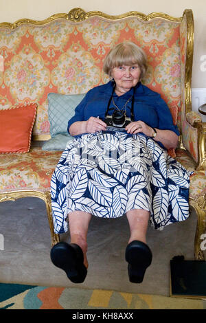 Photographer Jane Bown (13 March 1925 – 21 December 2014), portrait sitting on sofa holding camera - Stock Photo
