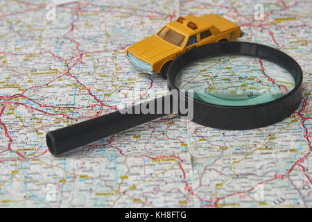 Magnifying glass and toy car on a map - Stock Photo