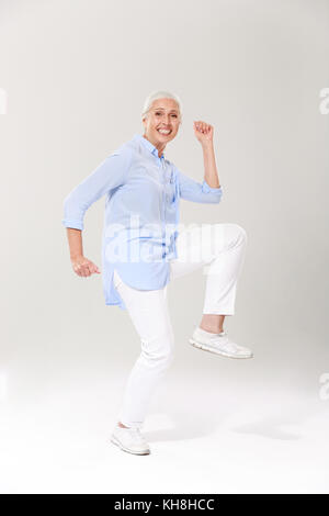 Full-length photo of playful old lady, having fun over white background - Stock Photo