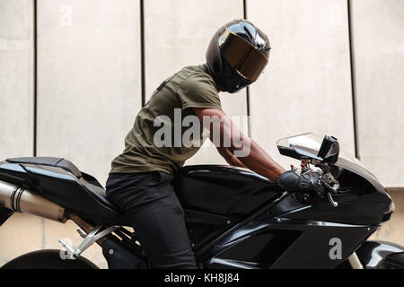 Portrait of an african man in helmet sitting on a motorbike outdoors - Stock Photo