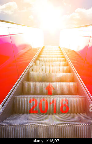 Ascending on an escalator with an arrow and 2018 written on it into sunlight. Concept photo for a successful new - Stock Photo