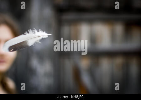 flying feather, the woman in the background - Stock Photo