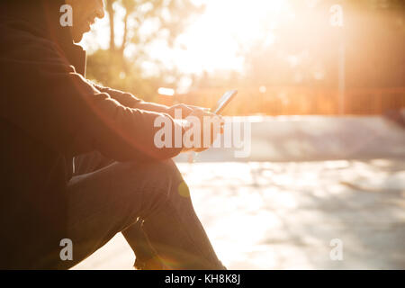 Cropped image of a smiling skateboarder looking at mobile phone screen on a sunlight background - Stock Photo