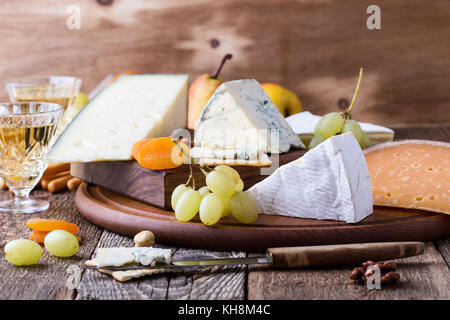 Cheese, fruit and wine wooden cutting board, delicious holiday appetizer on rustic table background - Stock Photo