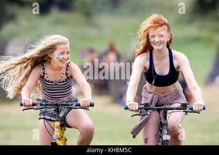 Youngsters riding their bikes near the Stone Circle at Glastonbury 2017 - Stock Photo
