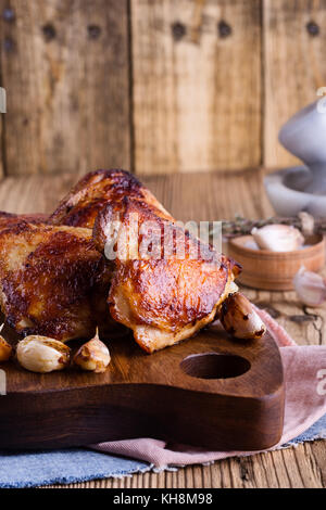 Roast chicken thighs with garlic  on rustic wooden cutting board - Stock Photo