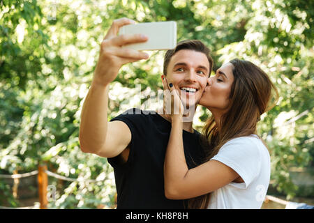 Portrait of a smiling happy man taking a selfie while his lovely girlfriend is kissing him at the park outdoors - Stock Photo