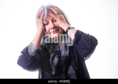 A grey haired senior adult elderly woman grandmother rubbing her forehead,, suffering from headache or migraine - Stock Photo