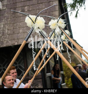 Wedding traditions in rural wales: Farming community friends of the bride and groom hold be-ribboned pichforks aloft - Stock Photo