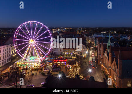 Illuminated Ferris wheel at evening Christmas market in winter at Koberg, Hanseatictown Luebeck, Germany - Stock Photo