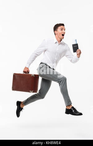Full length portrait of an amused happy man in white shirt holding passport with tickets and a suitcase while running - Stock Photo