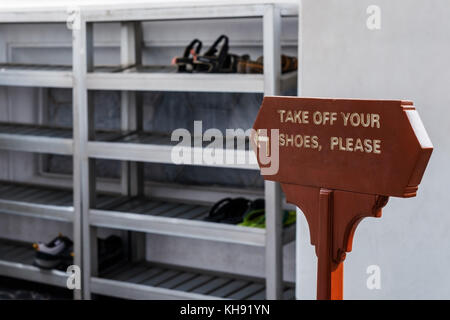 take off your shoes please. sign in english language - Stock Photo