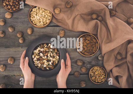 bowl with various nuts in hands - Stock Photo