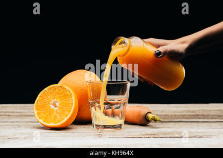 woman pouring fresh juice into glass - Stock Photo