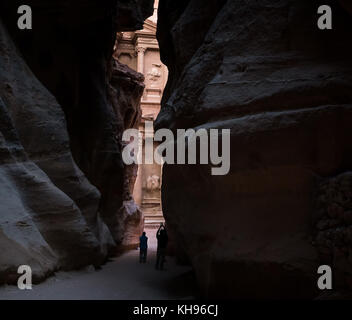 Pink sandstone Al Khazneh or Treasury through narrow gorge of Siq in early morning with a person taking a photo, - Stock Photo