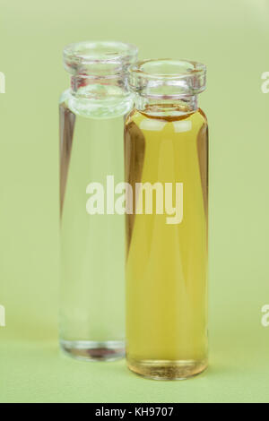 Homeopathic Extract - Closeup image of bottles containing a liquid homeopathic extract/liquid on a green background. - Stock Photo