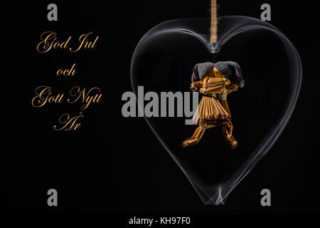 Christmas greetings in Swedish with dancing straw dolls in a rotating metal heart and with the text: God Jul och - Stock Photo